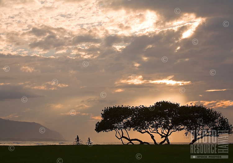 Mother and son push their bikes at sunset by the ocean at Haleiwa Alii Beach Park, Kaena Point in background, North Shore, Oahu, Hawaii