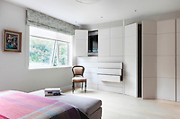 A spacious bedroom with a floor to ceiling built in wardrobe and an ottoma placed at the end of a double bed, which has a pink check pattern cover.