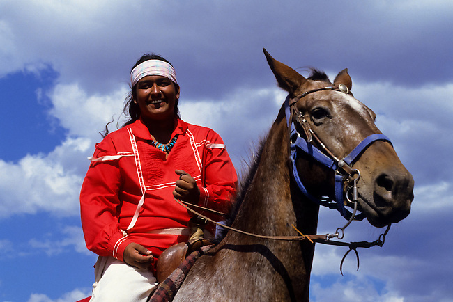 Taos Pueblo Indian with reed native dress on a horse in New Mexico, USA