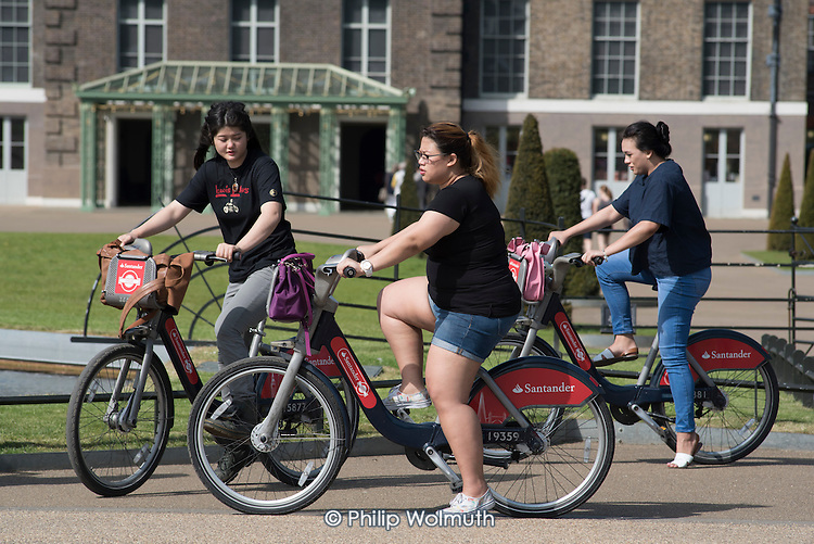 Tourists using Santander Cycles bicycle hire scheme, Kensington Gardens, London.