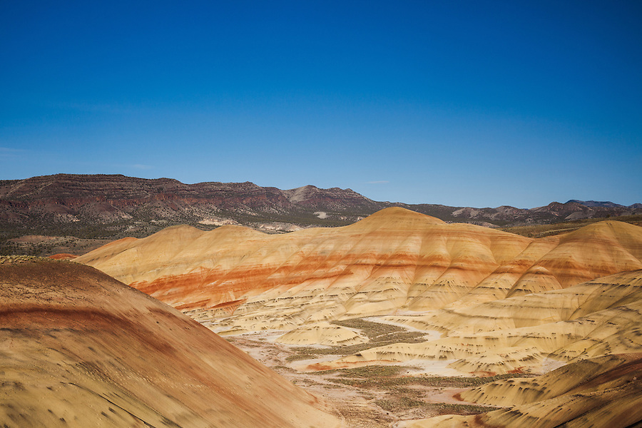 A section of the Painted Hills area of the John Day Fossil Beds National Monument is seen under a blue sky in the evening light near sunset in Wheeler County, Oregon.
