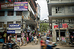 A busy street in Kathmandu, capital of Nepal. Seen through the buildings is a small wind turbine on the roof of a building.