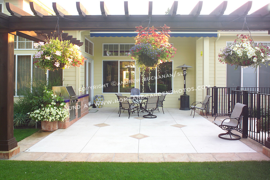 A decorative concrete and tile edged patio, bordered by an overhead arbor that hangs with baskets of colorful summer annuals, sits off the rear of this suburban hosue near Seattle and boasts a built-in grill and tile-topped counter work area.  Design by Sander Groves Landscapes, Inc.