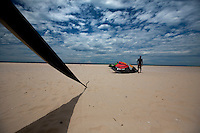 Binh, an employee at STORM Kiteboarding inflates a surf kite while waiting for the wind to pick up on Mui Ne beach.