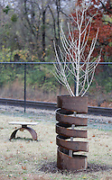 NWA Democrat-Gazette/DAVID GOTTSCHALK  The new sculpture Spiral, by artist Kody Fowler, accompanied by a small bench is on along the Frisco Trail on the Razorback Greenway Monday, November 16, 2015, in Fayetteville. Mayor Lioneld Jordan and the City of Fayetteville Parks and Recreation Department will host a ribbon cutting ceremony Thursday, November 18, 2015, at 1:00 p.m. for the new sculpture. The new sculpture has an Autumn Gold Ginkgo Tree planted in the center and is part of the Fayetteville Art Walk.