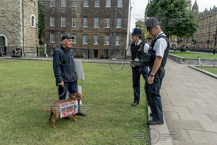 Police talk to a protestor whose dog is sporting an anti-nuclear weapons and vote 'leave' (the EU) placard outside Parliament.