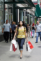 Montreal (Qc) CANADA, July 24, 2007 - Model Released photo- A young asian woman carrries a handfull of bags while shopping on Sainte-Catherine street West in Downtown Montreal.<br /> photo : (c) images Distribution