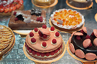 Cakes and tarts in a display window at a patisserie in Paris, France.
