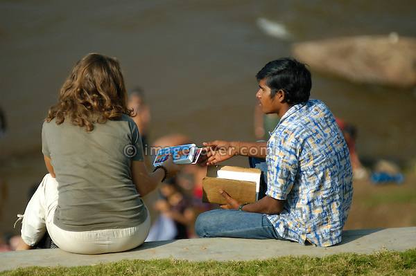 Indian man at the Tungabhadra River in Hampi selling postcards to a western female tourist. Hampi, Karnataka, India.