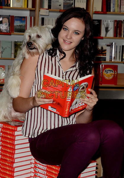 Ashleigh Butler and Pudsey .launch 'Pudsey My Autobidography' at Foyles bookshop, Charing Cross Road, London, England..10th October 2012.full length white purple sleeveless shirt striped stripes sitting trousers dog animal book books autobiography reading half 3/4 on shoulder.CAP/WIZ.© Wizard/Capital Pictures.