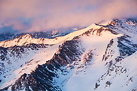 Aerial landscape of sunset light on the snow covered peaks of the eastern Alaska Range mountains.