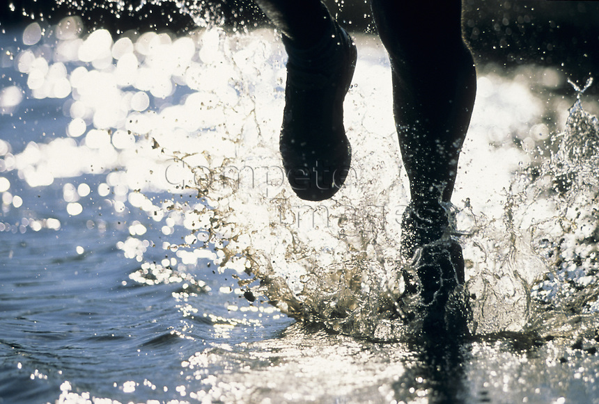 Silhouette of runner racing through water