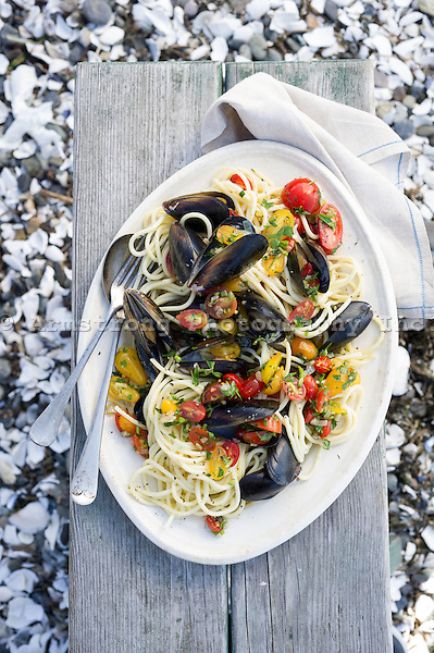 A large plate of mussels and linguine, with cherry tomatoes and parsley. Pictured on a picnic table with sand and shells visible behind it.