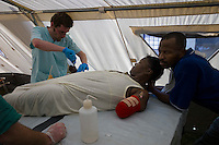 Port Au Prince, Haiti, Jan 23 2010.Islaine Celmé, 38, who lost her right hand and left arm in the disaster is comforted by her husband Carlo Celmé, 41; they are both displaying a very positive spirit in front of their personal tragedy. The Belgian B-Fast team has set up a field hospital in Delmas 33; 2 surgeons treat victims of heavy traumatisms..