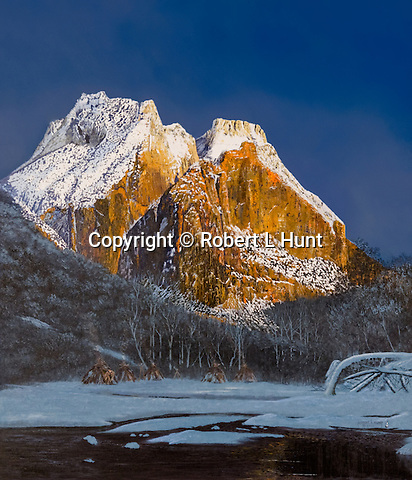 """Paiute Indian village lying in winter snow near the the base of a sunlit mountain, present day Zion National Park circa 1800. Oil on canvas, 35"""" x 30""""."""