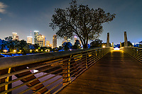 "The Carruth pedestrian Bridge over the Buffalo Bayou looking toward the Police Memorial with the Houston skyline after dark in the background.  You can see the blue lights that were install by the Kinder Fountation all  along the trail that turn the trees blue along with the Police Memorial. This was just one of many improvement that have been made in the parks.  On the Kinder Foundation site it states that this was ""Inspired by Buffalo Bayou Partnership's Sabine Promenade project and the organization's 2002 Master Plan, the Kinder Foundation approached Buffalo Bayou Partnership in 2010 to serve as the catalyst funder with a grant of $30 million, one of the largest gifts to Houston's park system, for improvements to the existing 160-acre, 2.3 mile stretch of the bayou from Shepherd Drive to Sabine Street. The project goal was to restore the area to a more natural and self-sustaining state, reintroduce native landscapes, and add amenities to enhance safety and convenience for visitors."""