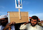 Male relatives carry the coffin of Ramadan Muhammad Barghout, 70, during the burial of eight bodies found last week in a mass grave near the town of Al-Qala in the Nefusa Moutains, Libya, Friday, Sept. 30, 2011. The eight were reburied next to 35 bodies found in a separate mass grave in the area. Members of the Amazigh indigenous tribe, the men were arrested from their homes and at checkpoints by pro-Gaddafi forces, imprisoned, and finally executed sometime in June. The men, many of them related as fathers and sons, or as brothers, were missing until the first, larger mass grave was found in mid-August.
