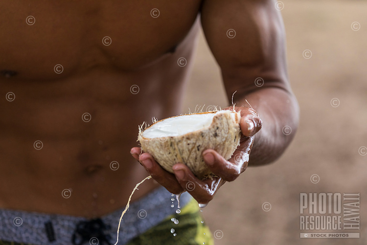 A young local man offers an open coconut he just harvested, Kaua'i.