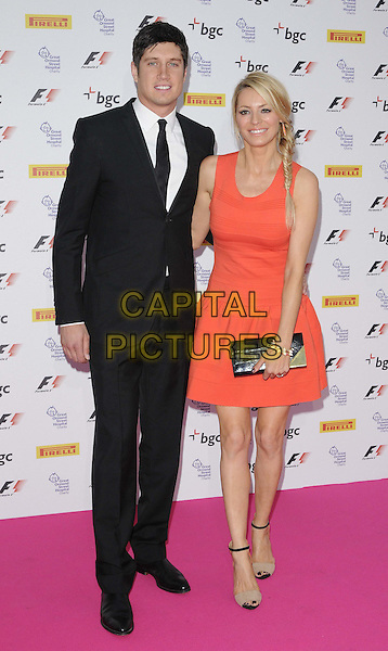 Vernon Kay & Tess Daly.The F1 Party fundraiser in aid of Great Ormond Street Hospital, Battersea Evolution, Battersea Park, London, England..July 4th, 2012.full length black suit white shirt tie orange dress clutch bag braid plait hair fishtail sleeveless married husband wife.CAP/CAN.©Can Nguyen/Capital Pictures.