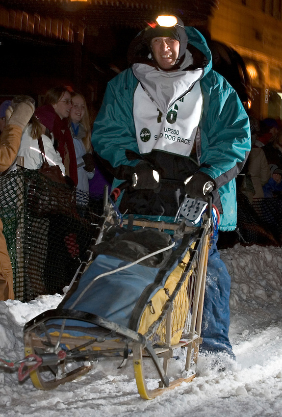 Crowds cheer as a musher rides through historic downtown Marquette, Mich. during the U.P. 200 Sled Dog Championship.