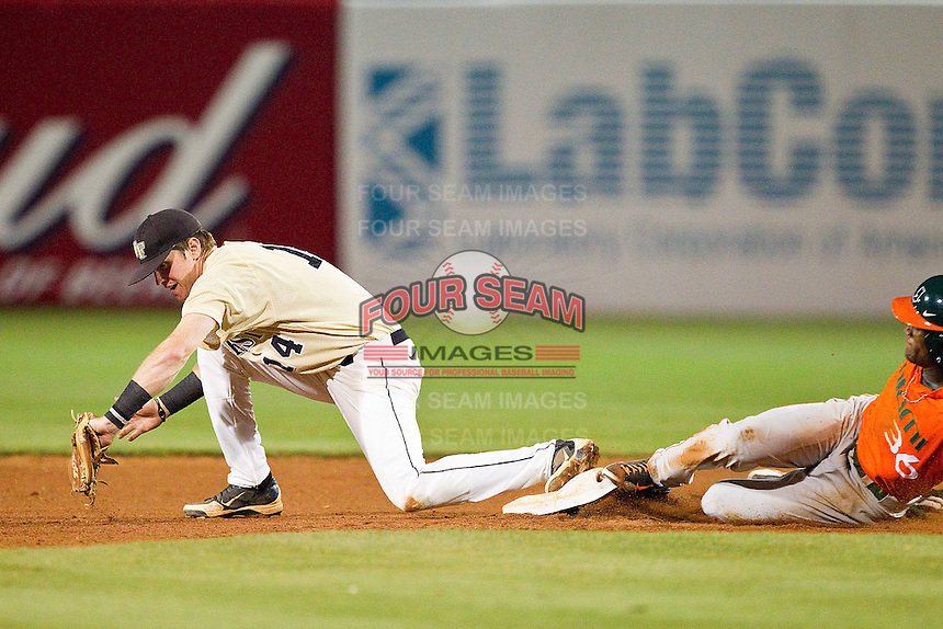 Conor Keniry #14 of the Wake Forest Demon Deacons stretches for a throw at second base during the game against the Miami Hurricanes at NewBridge Bank Park on May 25, 2012 in Winston-Salem, North Carolina.  The Hurricanes defeated the Demon Deacons 6-3.  (Brian Westerholt/Four Seam Images)