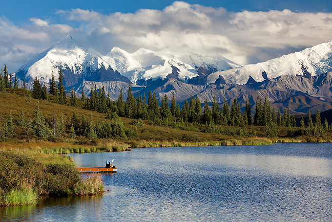 A tourist relaxes on a dock amidst the breathtaking landscape in late day, Wonder Lake, Denali National Park.