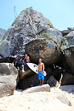 BRAZIL, Rio de Janiero, two friends hang out on the rocks at Prainha Beach