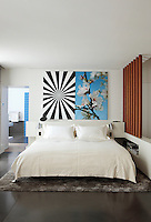 """Exstacy Almond Blossom 2"", a work by Mustafa Hulusi hangs above the bed in this contemporary bedroom"