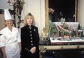 First lady Hillary Rodham Clinton poses with the traditional White House gingerbread house in the State Dining Room of the White House in Washington, D.C. on December 5, 1994.  President Clinton's boyhood home in Hope Arkansas is the inspiration for this year's gingerbread house.  White House Master Pastry Chef Franett McCulloch at left.<br /> Credit: Ron Sachs / CNP