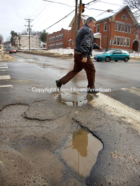 WATERBURY, CT. 07 February 2011-020711SV01--Veckman Santiago of Waterbury crosses Washington Avenue while trying not to step in pothole in Waterbury Monday.<br /> Steven Valenti Republican-American