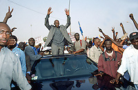 Senegal. Dakar. Political meeting. Opposition leader Abdoulaye Wade from the FRTE party greets a crowd of supporters by waving both arms and hands. His car, a Mercedes, goes slowly through the public. Abdoulaye Wade will later defeat his opponent  Abdou Diouf in the election results and will be  appointed as the new president of Senegal. © 2000 Didier Ruef