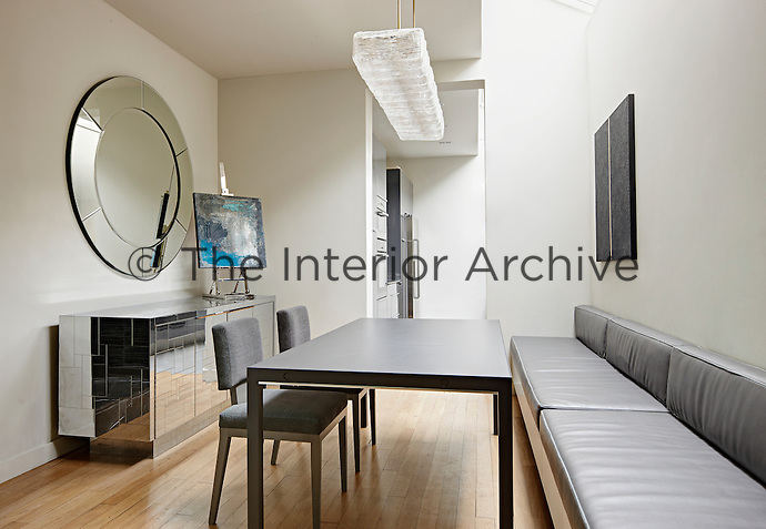 A modern dining room adjoins a kitchen. The room is simply furnished with a grey leather banquette seat and a plain dining table and two chairs. A large round mirror hangs above a mirrored sideboard.