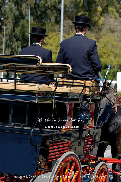 Two coachmen driving a barouche carriage during the Seville Spring Fair, Seville, Andalusia, Spain.