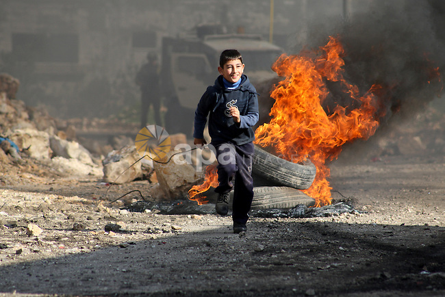 A Palestinian boy runs back after during clashes with Israeli security forces in a protest against the expropriation of Palestinian land by Israel following Friday prayers in the village of Kafr Qaddum, near Nablus, November 28, 2014. According to reports, some 20 Palestinians were wounded during the clashes. Photo by Nedal Eshtayah