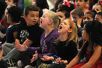 NWA Media/ J.T. Wampler - Tyler Boysen, left, and Audrey Fox sing Thursday Dec. 18, 2014 during the Rogers Northside Elementary School holiday sing-a-long. The annual holiday event also featured Academy Sports + Outdoors donating bikes and helmets to 30 deserving students (15 girls and 15 boys) as part of Academy's annual bike donation program.