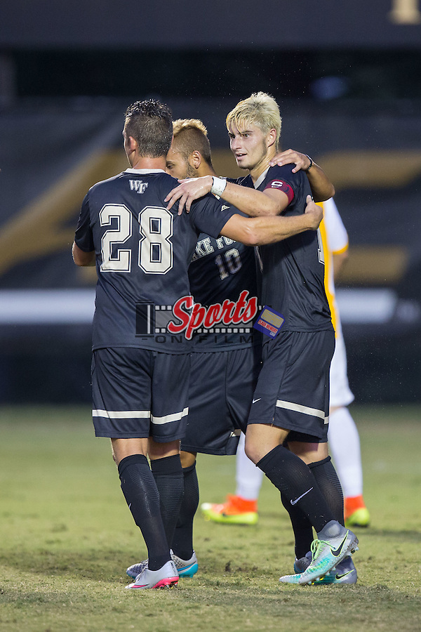 Ian Harkes (16) of the Wake Forest Demon Deacons is congratulated by teammates Tane Gent (28) and Bruno Lapa (10) after scoring a goal on a penalty kick during first half action against the Appalachian State Mountaineers at Spry Soccer Stadium on September 6, 2016 in Winston-Salem, North Carolina.  The Demon Deacons defeated the Mountaineers 3-0.   (Brian Westerholt/Sports On Film)