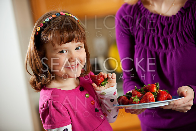 Little Caucasian girl in the kitchen, having snacks like strawberries and grilled cheese.