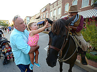 NWA Democrat-Gazette/BEN GOFF @NWABENGOFF<br /> Kyle Willis of Olive Branch, Miss. holds his daughter Raegan Willis, 2, up to pet the horse of Ron 'Horseshoe' Hodge of Springdale on Friday Sept. 4, 2015 after Hodge took part in a re-enactment of an 1893 bank robbery during First Friday September: Sugar Creek Days on the Bentonville square. The re-enactment was based on the June 5, 1893 robbery in which outlaw Henry Starr and five men made off with cash from the People's Bank of Bentonville after a shootout with civilians and the sheriff.