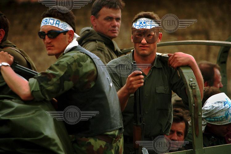 Serb paramilitaries ride on a convoy leaving Kosovo during the war.