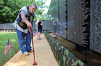 NWA Democrat-Gazette/DAVID GOTTSCHALK  Vietnam War and Air Force veteran Greg Weeks, 1967-1971, reflects Thursday, May 18, 2017, as he looks for service members on the Vietnam Veterans Memorial The Moving Wall following opening ceremonies on the campus of the Veterans Health Care System of the Ozarks in Fayetteville. The wall has been touring the country for more than 30 years and will on the camus through Monday, May 22. The Moving Wall is a half scale replica of the memorial in Washington D.C..