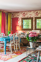 Colourful striped curtains screen the window in the dining area which is furnished with a turquoise-painted table and a bright pink painted wall-mounted radiator