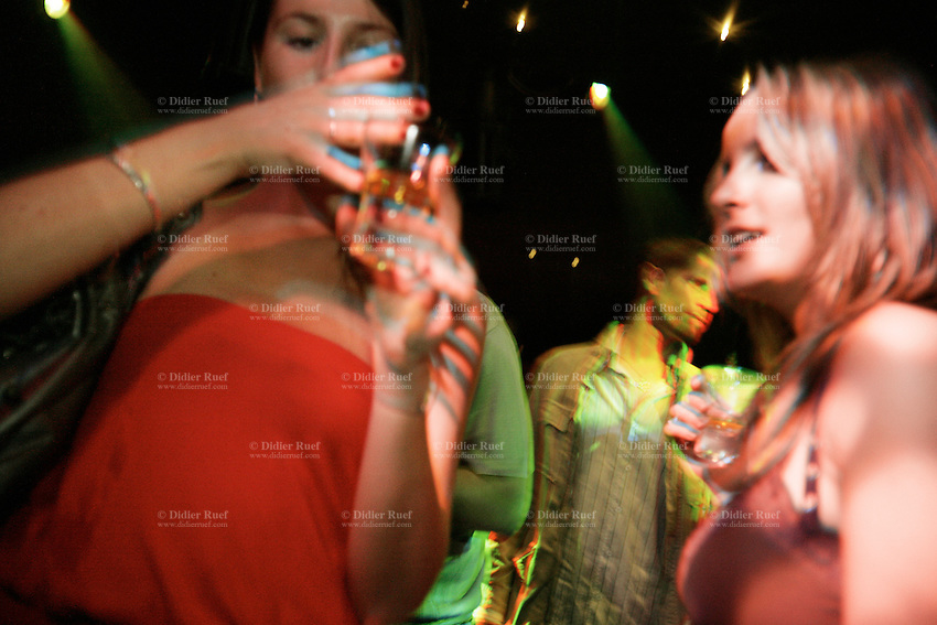 Switzerland. Canton Vaud. Lausanne. Red club. Exclusive and VIP party for the lauch of Xellent Vodka, the first and only Swiss Vodka. Two young girls have a drink on the dance floor. Night life. © 2006 Didier Ruef