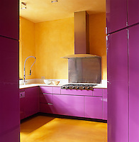 This contemporary kitchen makes a loud and colourful.statement combining yellow walls with lacquered pink kitchen.units
