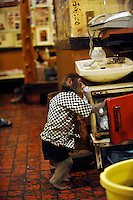 Fuku-chan, 6, a Japanese monkey waiter, gets hot towels from an oven in an Izakaya bar in north of Tokyo, Japan. The six year old monkey looks after the guests hot towels by taking them from the steamer oven and delivering them to all guests. The bar is extremely popular amongst people from all over Japan who come to see the monkey waiters.
