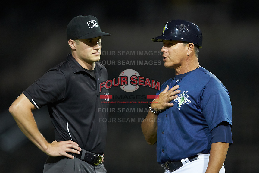 Columbia Fireflies manager Pedro Lopez (right) discusses a call with umpire Evin Johnson during the game against the Rome Braves at Segra Park on May 13, 2019 in Columbia, South Carolina. The Fireflies defeated the Braves 6-1 in game two of a doubleheader. (Brian Westerholt/Four Seam Images)