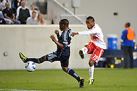 Dane Richards (19) of the New York Red Bulls passes the ball as Korede Aiyegbusi (3) of Sporting Kansas City defends. The New York Red Bulls defeated Sporting Kansas City 1-0 during a Major League Soccer (MLS) match at Red Bull Arena in Harrison, NJ, on April 30, 2011.
