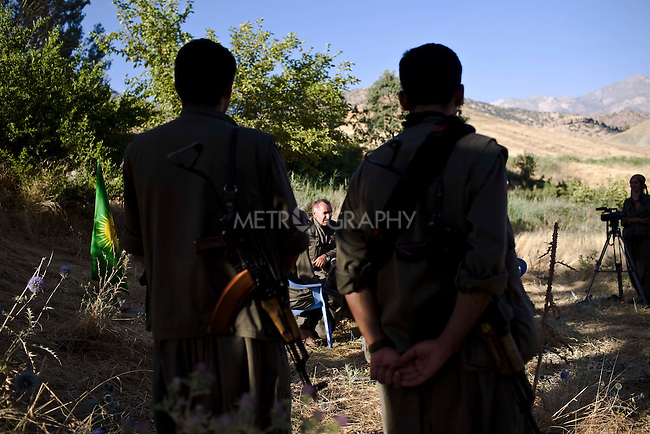 QANDIL, IRAQ: Two guerrillas with the Kurdistan Worker's Party (PKK) stand guard over their acting leader, Murad Qarayilan (center) as he gives an interview...The Kurdistan Workers' Party (PKK) is a Kurdish organization fighting for Kurdish autonomy in Turkey.  It is deemed a terrorist group by the USA and the EU. The organization's guerillas are based in the Qandil mountains that make up the border between Iraq and Turkey..Photo by Kamaran Najm / Metrography