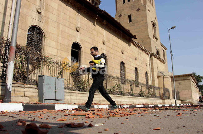 An Egyptian man walks outside the Saint Peter and Saint Paul Coptic Orthodox Church in Cairo's Abbasiya neighbourhood after it was targeted by a bomb explosion on December 11, 2016, . The blast killed at least 25 worshippers during Sunday mass inside the Cairo church near the seat of the Coptic pope who heads Egypt's Christian minority, state media said. Photo by Amr Sayed