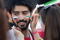 SARANSK, RUSSIA - June 25, 2018: An Iran fan has his face painted in Millennium Square in Saransk before the 2018 FIFA World Cup group stage match between Iran and Portugal at Mordovia Arena..