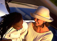 African-American Woman and Hispanic Woman laughing together in convertible car; female bonding; friendship; Black, Latina women. Kim Mayes, Kimberly S. Garcia.